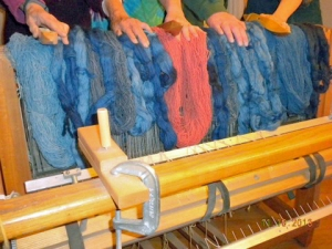 dyed yarn skeins hanging on the back of a loom