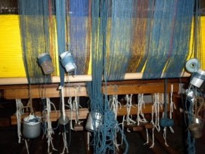 Because of the differences in the elasticity of the warp yarns, the back of the loom became a mess. We hung weights on the loom to keep tension on the yarns.