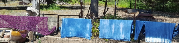 indigo dyed garments hanging on the fence