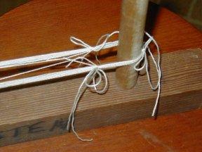warp threads tied around a post